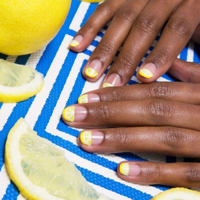 manos de mujer morena con uñas amarillas de limones