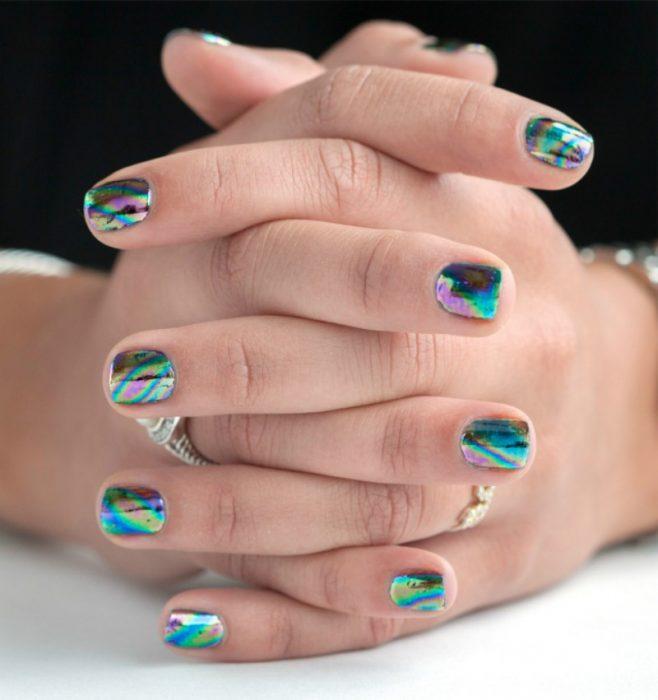 manos de mujer con uñas holograficas