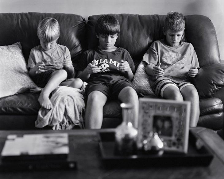 niños en un sillon sentados sin viendo sus manos