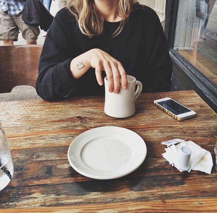 mujer rubia con tatuaje tomando café y celular en la mesa
