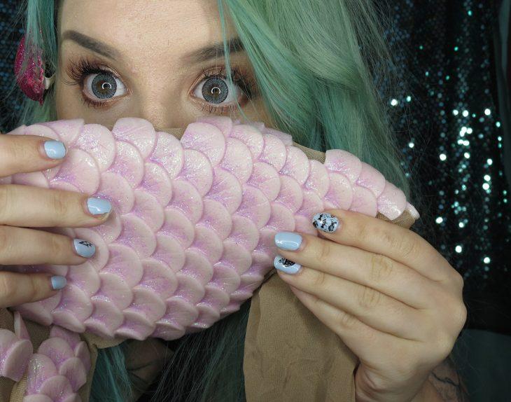 mujer de cabello verde con escamas de pescado en su cara