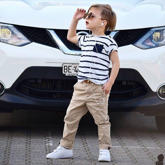 Niño mini fashionista vestido con un pantalón color caqui, camisa a rayas y tenis blancos