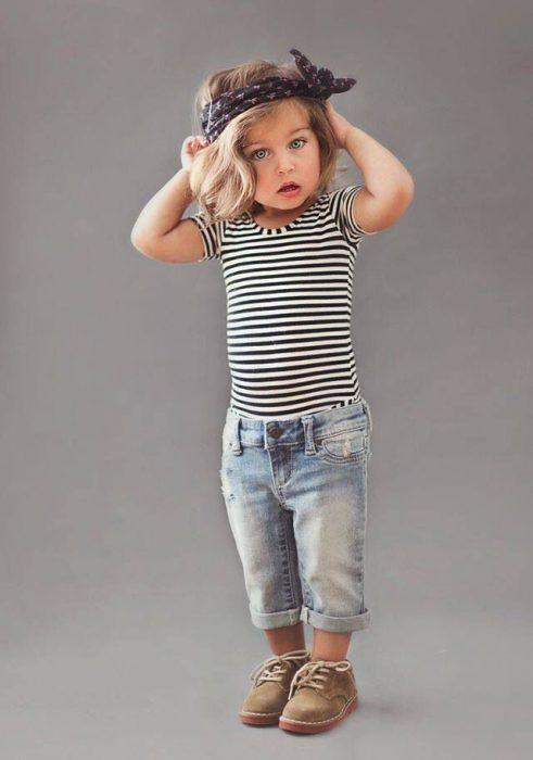 Niña mini fashionista vestida con una playera a rayas, pantalón de mezclilla y botas