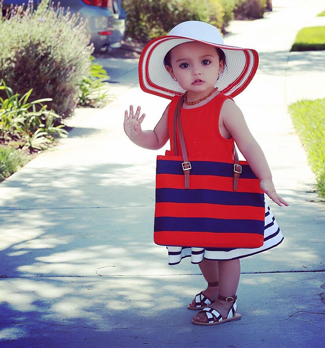 c9711001 Niña mini fashionista usando un vestido color rojo, bolso de rayas azules y  rojas y