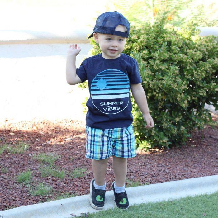 Niño mini fashionista con bermidas, camisa azul y gorra