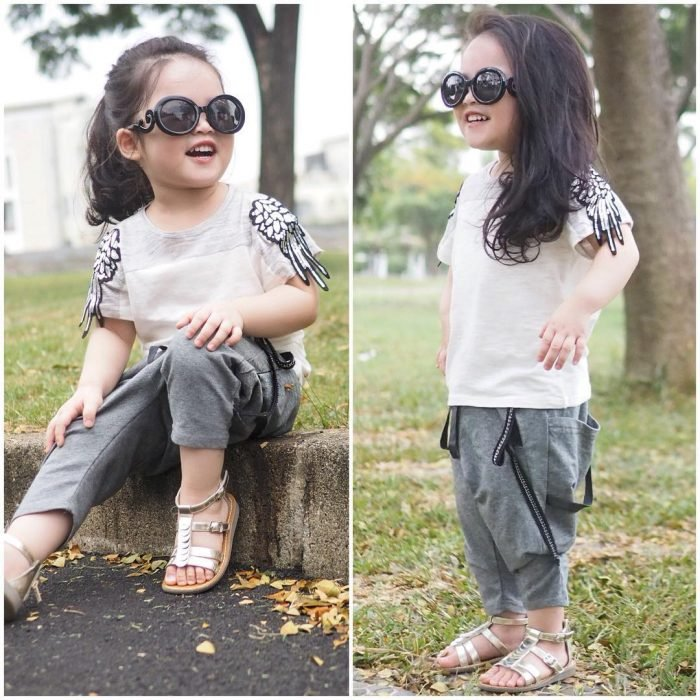 Niña mini fashionista usando pantalones de chandal, camisa y huaraches