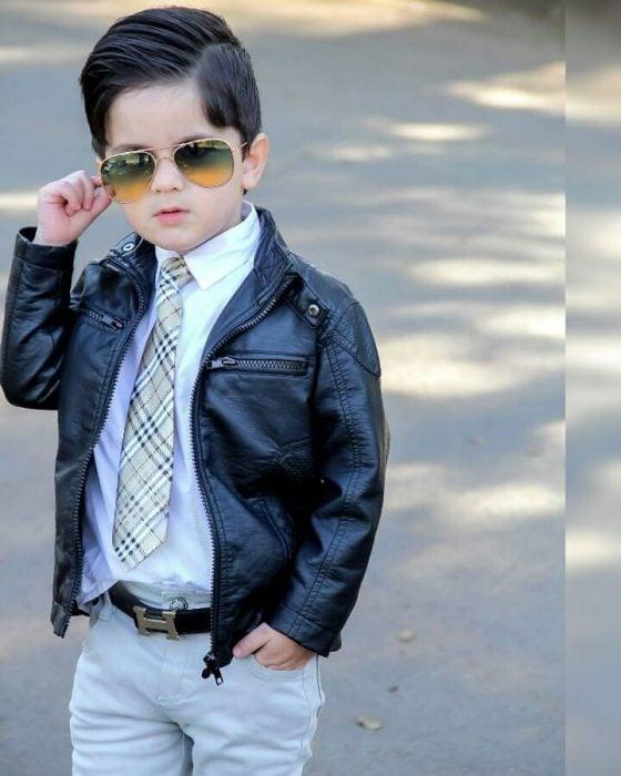 Niño mini fashionista usando chamarra de piel, camisa de vestir y corbata