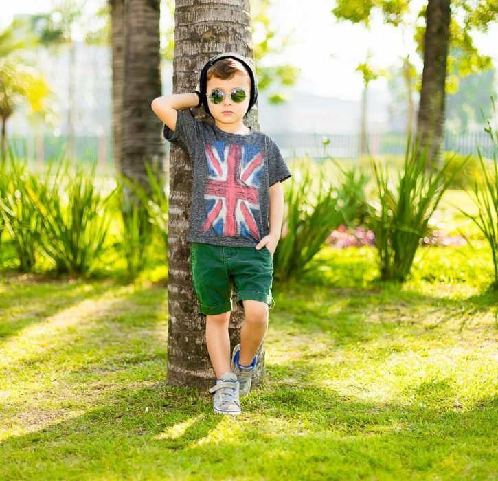 Niño minifashionista usando bermodas verdes y camisa gris con converse gris