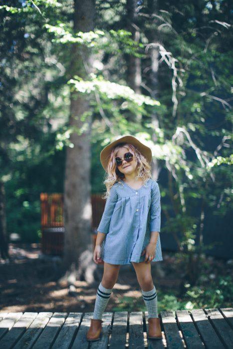 Niña mini fashionista usando un vestido de mezclilla sombrero y espartanas en medio de un jardín