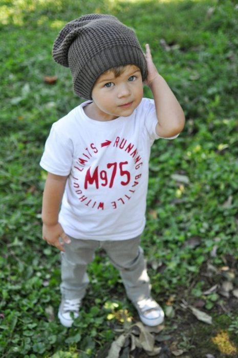 Niño mini fashionista vestido con un pantalón color gris, playera blanca y gorra color gris