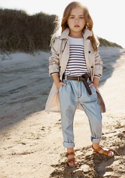 Niña fashionista vestida con una chaqueta, pantalón de mezclilla y sandalias mientras está parada frente al mar