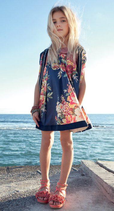 Niña mini fashionista vestida con un vestido playero y zapatos