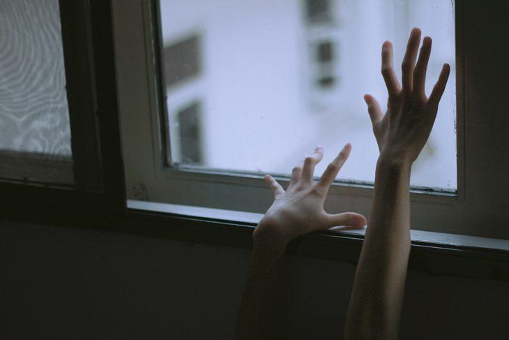 manos de mujer arrastrándose en la ventana