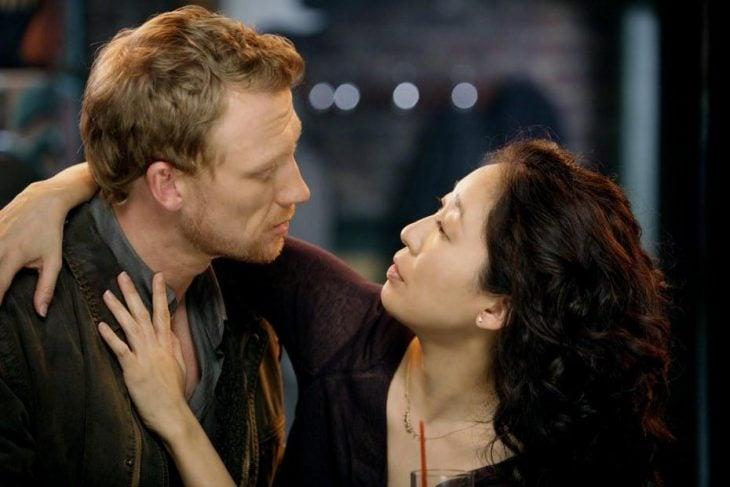 hombre rubio abrazado de mujer de cabello negro