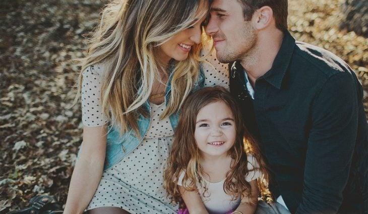 mujer rubia al lado de hombre mientras niña pequeña esta en medio