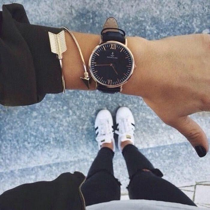 mano de mujer con reloj y pies con tenis