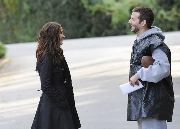 hombre frente a mujer sonriendo y balon de fubtol