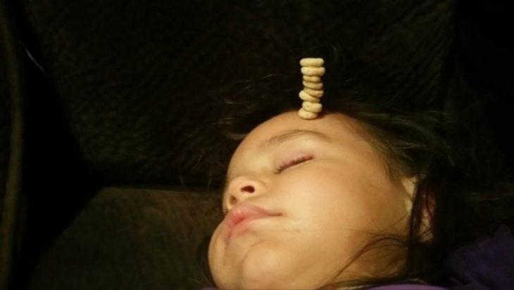 bebe dormido con pila de cereal en su frente