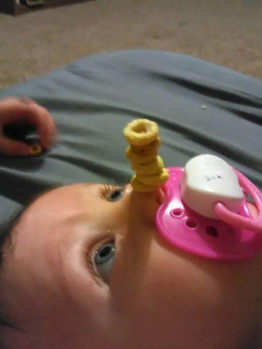 bebe con chupon y pila de cereal en la nariz