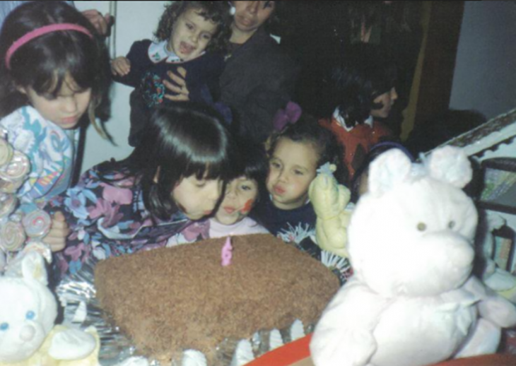 niña soplando vela de pastel