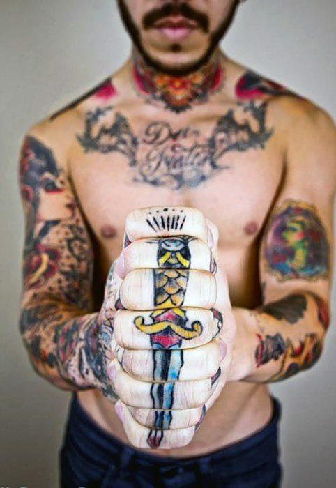 Chico juntando sus manos para formar un tatuaje de espada