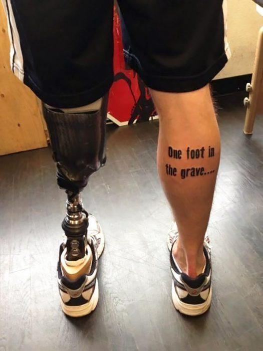 Chico sin una pierna con un tatuaje en la otra que dice con un pie en la tumba