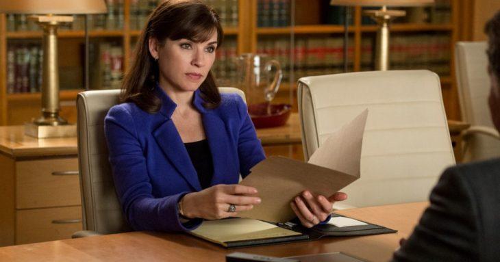 mujer de saco azul y cabello corto sentada en escritorio