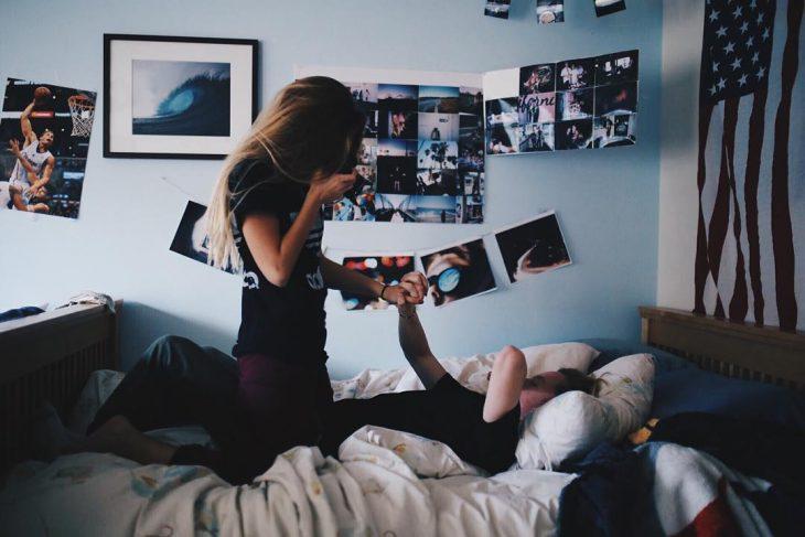 hombre acostado en la cama y mujer le toma una foto