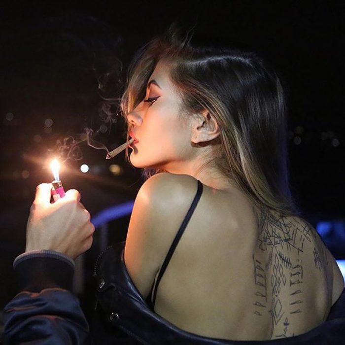 mujer de cabello rubio de espaldas prendiendo un cigarro