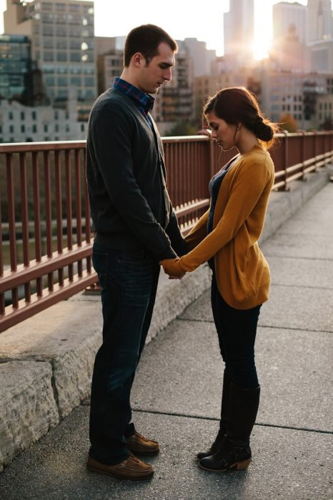 pareja tomados de la mano con los ojos cerrados y miran hacia abajo