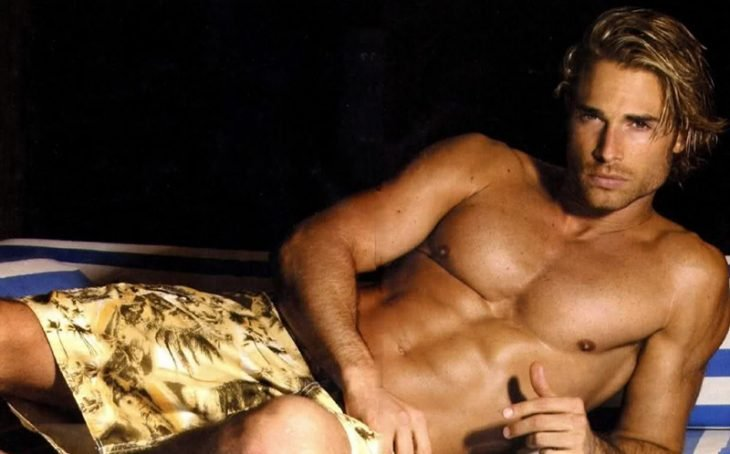 hombre bronceado sin camisa acostado en cama