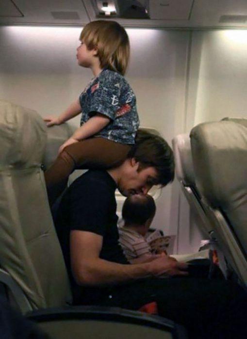 niño rubio sentado en el cuello de hombre en asiento de avión
