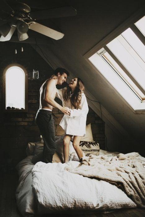 Pareja de novios sobre una cama riendo