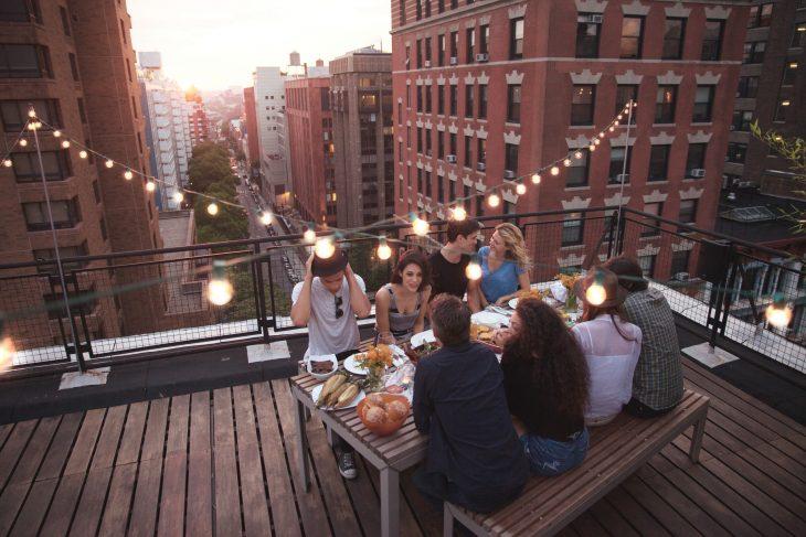 Chicos y chicas comiendo la cena sobre una terraza