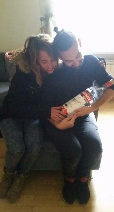 pareja con una botella como si fuera bebé