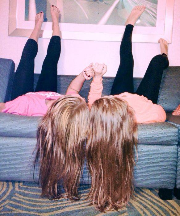 chicas en un sillón con pies hacia arriba