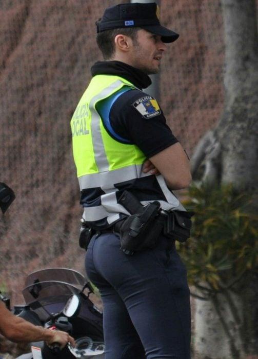 hombre policia de espalda con chaleco fosforecente