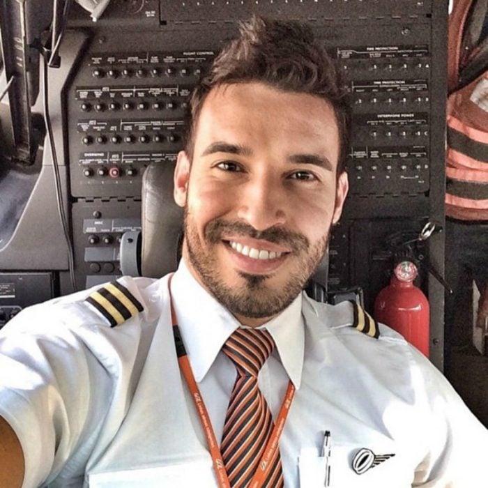 hombre con camisa de piloto en cabina de avion