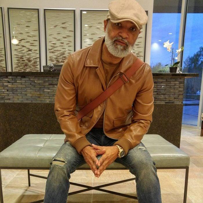 hombre moreno con barba sentado con chamarra de píel y gorra
