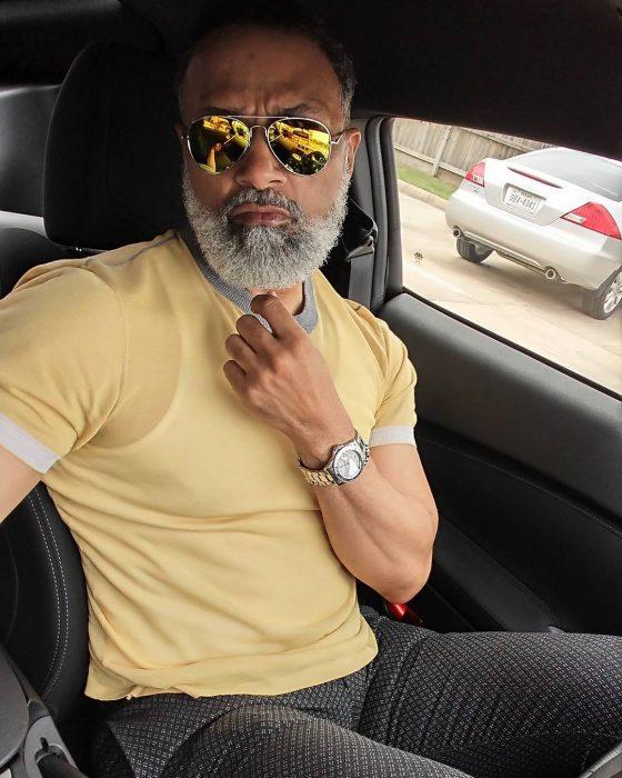 hombre moreno con músculos y barba sentado en coche