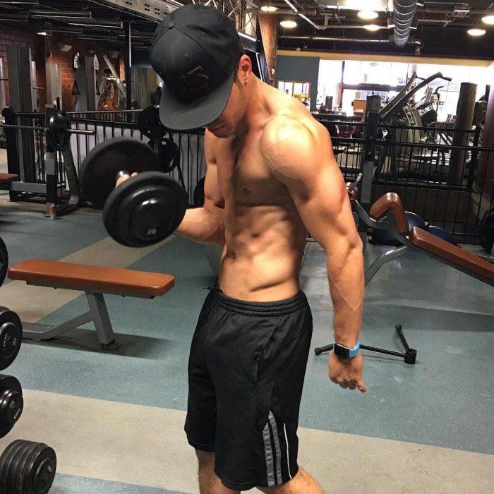 hombre musculoso haciendo pesas en gimnasio