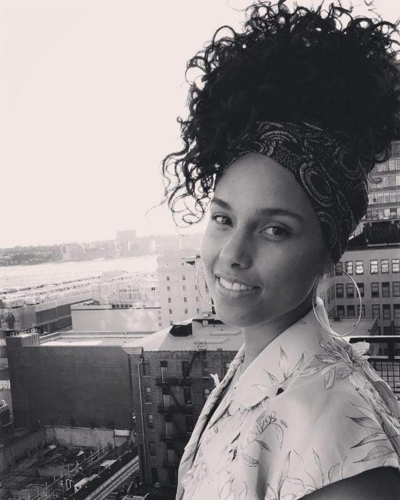 Mujer morena con rizos en un balcón de una cuidad