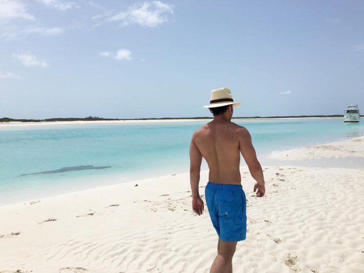 hombre moreno sin playera con sombrero en la playa