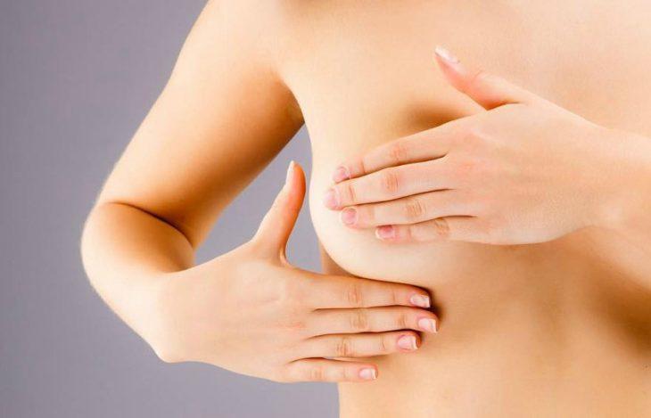 manos de mujer auto explorándose los senos