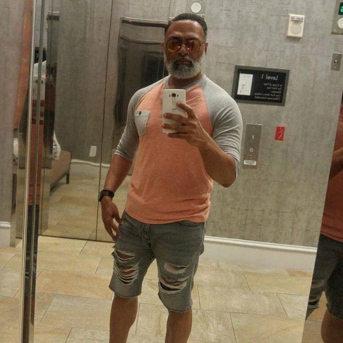 hombre moreno con músculos y barba hace selfie frente espejo