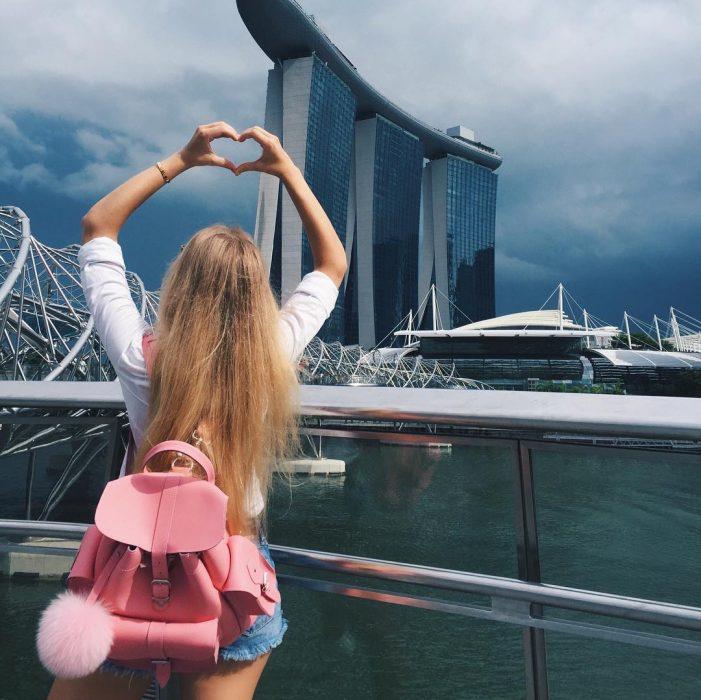 mujer rubia con mochila rosa en cuidad hace corazon con manos