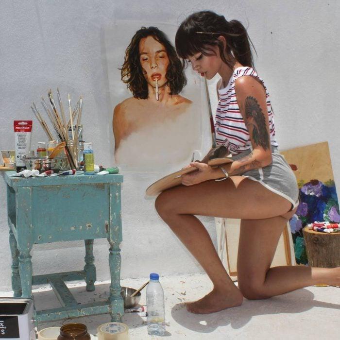 mujer morena hincada pintando retrato