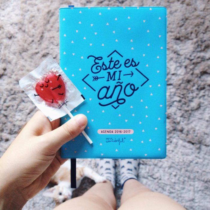 mujer con paleta roja y una agenda azul