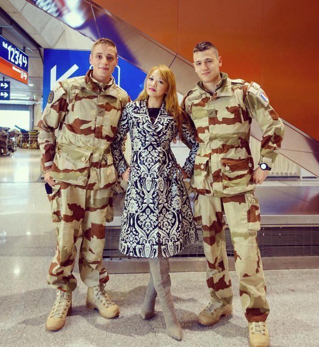 dos hombres soldados en aeropuerto con mujer rubia