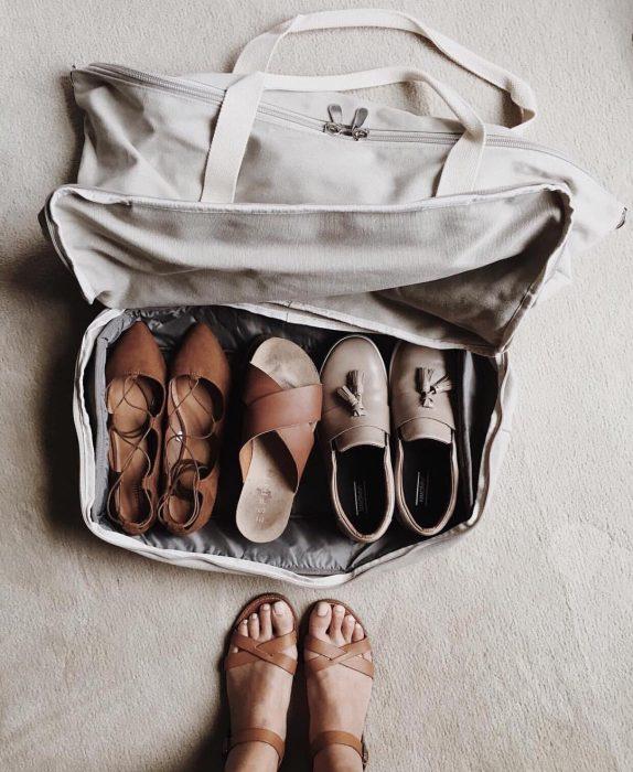 maleta con pares de zapatos y unos pies